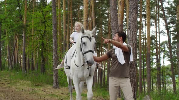 Little Girl Riding Horse Led by her Father