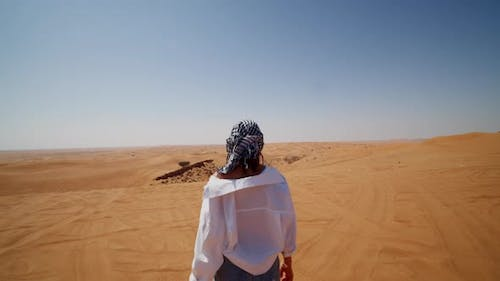 Young Caucasian Woman with Scarf and Sunglasses Walking Around Sand Dunes in the Desert