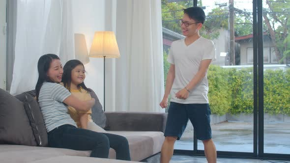 Happy young Asian family listen to music and dancing on couch at home.