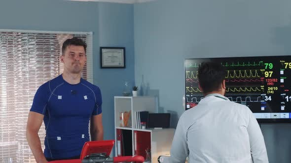 Handsome Athlete Being Tested and Monitored By Multiracial Doctor During Treadmill Test in Lab