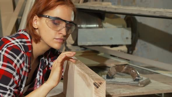 Thumbnail for Female Carpenter Examining Wooden Plank After Sanding 1080p