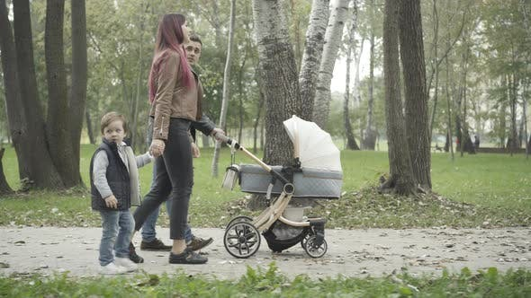 Side View of Relaxed Young Family Strolling in Spring or Summer Park and Talking