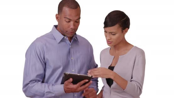 Thumbnail for Two African American business professionals discuss work on their tablet on a white background