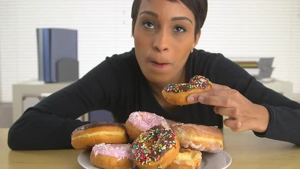 Thumbnail for African American business woman eating a pile of donuts