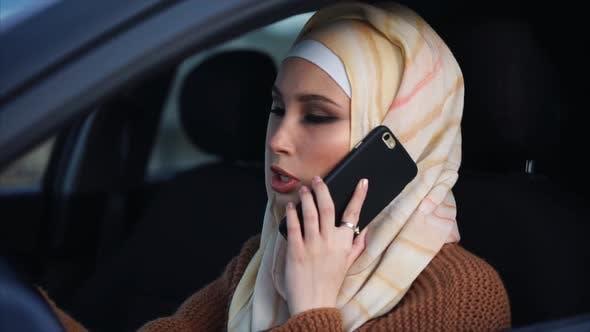 Thumbnail for Modern Muslim Woman Having a Phone Talk at the Wheel