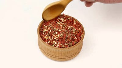 Chef Taking Chopped Dry Dried Tomatoes Chili and Other Spices From Wooden Spice Jar