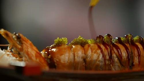Werkzeug gießen Sauce auf Sushi.