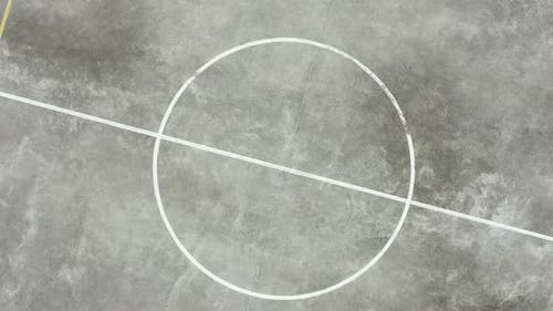 Top view of the circle in the middle of a basketball field and zooming out