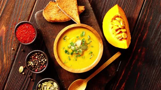 Pumpkin Soup with Bread on Chopping Board