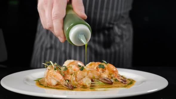Thumbnail for Close Up of Green Sauce Being Poured in Line Across Freshly Prepared Prawns Placed on White Plate in
