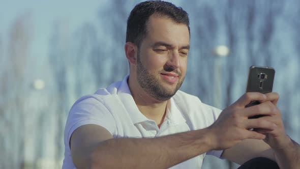 Thumbnail for Smiling Bearded Man with Smartphone During Summer Sunny Day