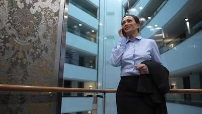 Businesswoman Talking on Smartphone in Hotel Lift