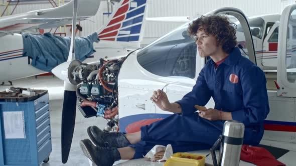 Thumbnail for Female Aircraft Technician Having Lunch in Hangar