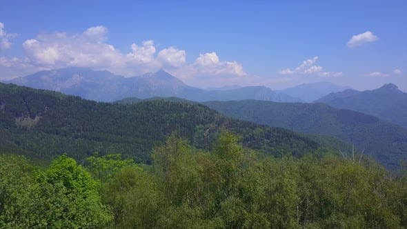 Thumbnail for Drone Flying Over Green Trees Overlooking Mountain Peaks and Hills Covered with Green Forest