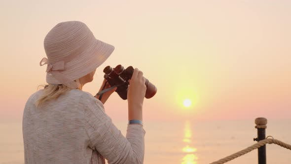 Thumbnail for A Young Woman Looking Through Binoculars in the Distance To Meet a Pink Dream, Sits on a Sea Pier in