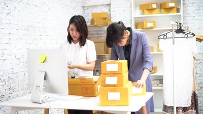 Women Packing Goods in Boxes