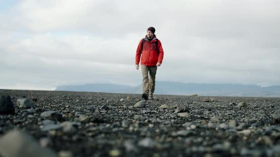 Thumbnail for A View of a Man Legs in Boots Walking on Black Sand and Stones on a Beach in Iceland.