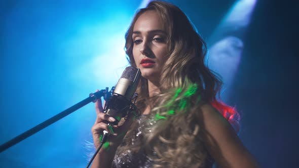 Thumbnail for Beautiful Woman Blonde Sings On Stage In Microphone