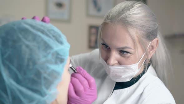 Thumbnail for Cosmétologue applique le tatouage permanent sur les sourcils de fille