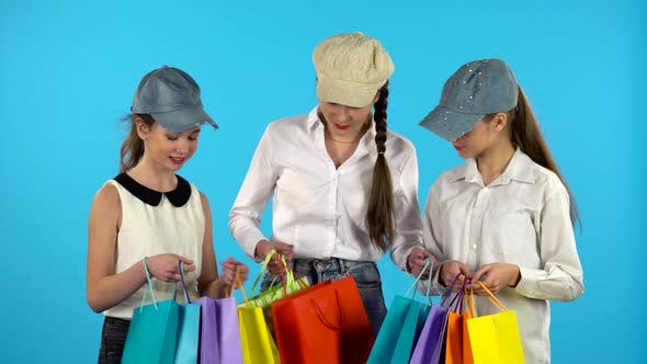 Thumbnail for Three Girl Shopper Looks in Shopping Paper Bagand and Happy, Blue Background