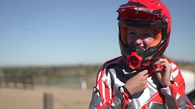 A young woman bmx rider putting on helmet.