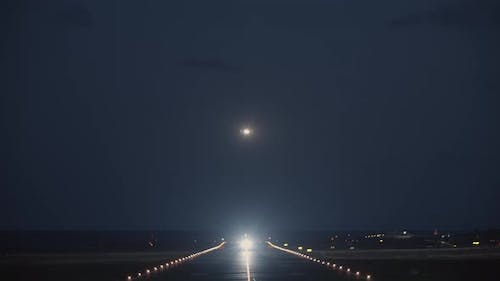 A Night View of a Runway with a Taking Off Plane