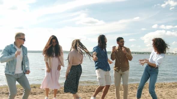 Slow Motion of Men and Women Dancing on Lake Shore Having Fun During Beautiful Simmertime Vacation