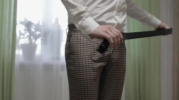 Thumbnail for Der  Bräutigam trägt einen Gürtel. Mann in weiß Hemd legt Gürtel auf seine Hose in Hochzeit Morgen