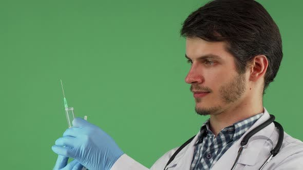 Thumbnail for Male Medical Worker Holding a Syringe on Green Background