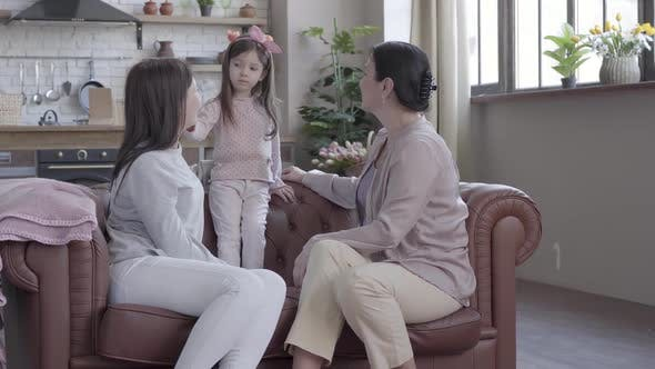Cover Image for Grandmother, Mother and Little Daughter Spend Time Together Sitting on the Sofa in Modern Apartment