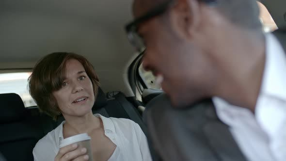 Thumbnail for Businesswoman Drinking Coffee and Talking with Taxi Driver in Car
