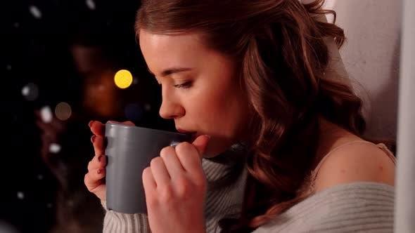 Frau mit Kaffee oder Teetasse auf Fensterbank zu Hause