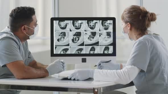 Männliche und weibliche Ärzte diskutieren CT-Scan auf Lungen