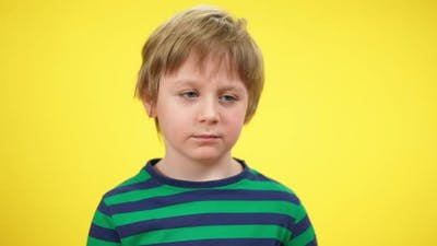 Closeup Portrait of Tired Little Boy Yawning at Yellow Background