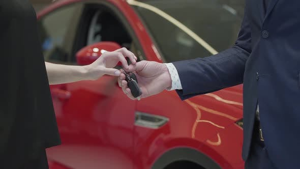 Cover Image for Unrecognized Salesman in a Business Suit Gives a Car Keys To Unrecognized Businesswoman and Shake Hands