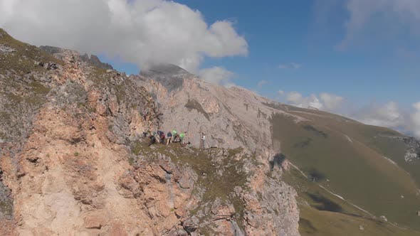 Thumbnail for Aerial Shot of a Group of Climbers on Top of a Mountain Pulling a Rope.