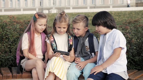 Thumbnail for Four gadget addicted kids sitting in the park and looking