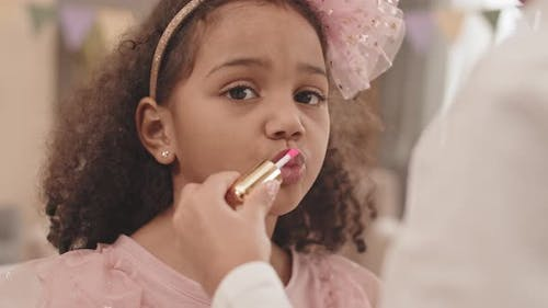 Girl Painting Lips with Gloss