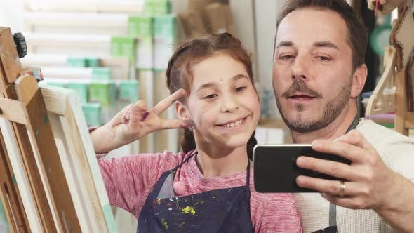 Thumbnail for Happy Father and Daughter Taking Selfies at Art Studio While Painting