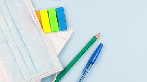 Schulmaterial liegt auf einem pastellblauen Hintergrund mit einer medizinischen Maske