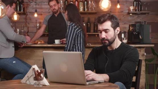 Junge gutaussehende Mann tippt eine Nachricht auf seinem Laptop beim Entspannen in einem Vintage Coffee Shop