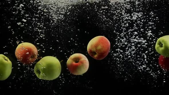 Cover Image for Ripe Fruits Colorful Apples Falling Into Water with Splash and Bubbles Black Background