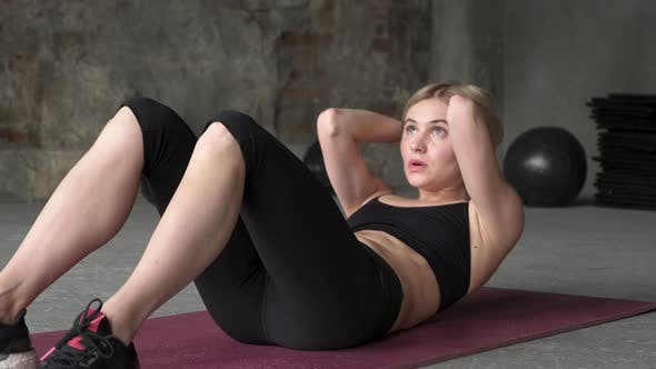 A young girl shakes the press. Girl shakes her abdominal muscles. Sporty woman in gym.
