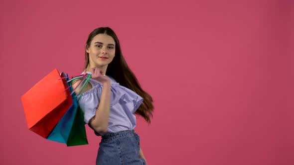 Thumbnail for Girl with Shopping Bags Is Standing with Her Back Turning and Winking. Pink Background