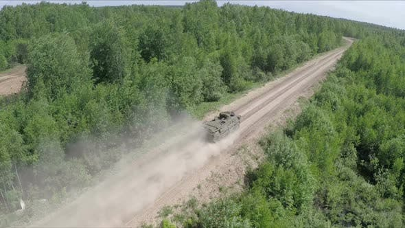 Flying Over the Military Vehicle Driving in Rough Wooded Country