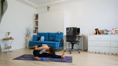 Young Woman Doing Yoga Pose Dedicated To The Sage Marichi I At Home