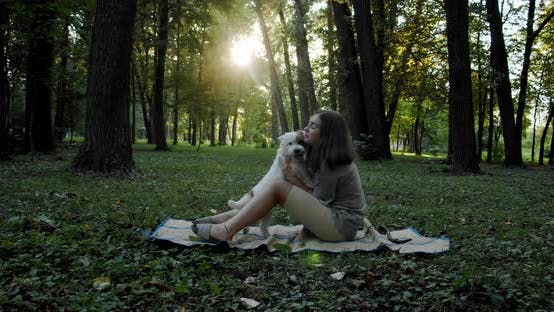 Thumbnail for Teenage Girl Is Sitting with a Cute Pets on a Green Lawn in the Sunset. Happy Dog