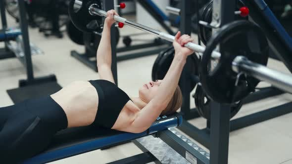 Young Slim Woman Raises a Weight with Both Arms in the Fitness Club