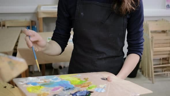 Thumbnail for Woman with Apron on Her Body Is Drawing on Easel in Art Workshop
