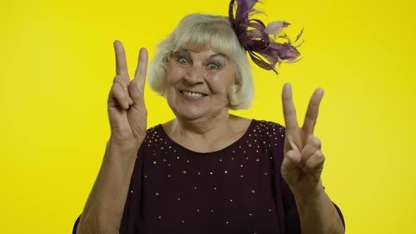 Thumbnail for V-Zeichen, Frieden. Happy Senior Alte Frau zeigt Siegeszeichen mit Doppelfinger und Lächeln